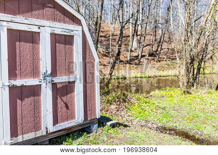 Old Red Shed With Lock And Many Yellow Lesser Celandine Flowers In Meadow By River
