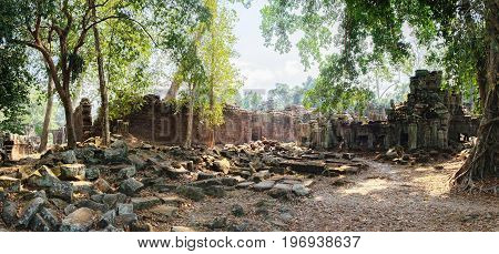 The ancient ruins of the Preah Khan Temple in Siem Reap, Cambodia. Road to the temple among a pile of stones and tropical trees. Ancient Khmer architecture, famous Cambodian landmark, World Heritage