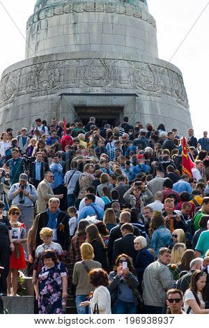 BERLIN - MAY 09 2015: Victory Day in Treptower Park. Many visitors to lay flowers at the monument to the Liberator Soldier.