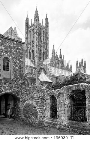 Canterbury Kent United Kingdom - June 17 2006: Girl tourist visiting the Canterbury Cathedral courtyard. It is one of the most famous cathedrals in England. Black and white.