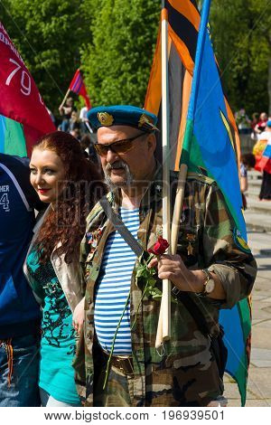 BERLIN - MAY 09, 2015: Man with patriotic flags and uniform paratrooper.