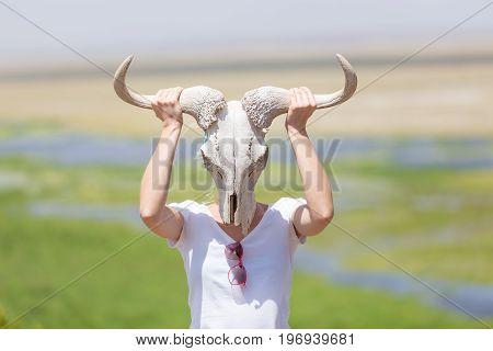 Woman holding a white wildebeest skull wearing it like a mask in nature on african wildlife safari, Amboseli national park, Kenya.