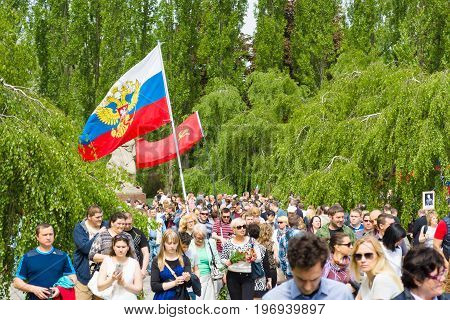 BERLIN - MAY 09, 2015: Visitors to the memorial with the flags of the USSR Russia and patriotic slogans.