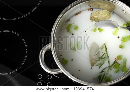 Cooking pot with flavored brine for turkey on stove