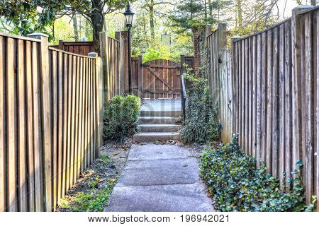 Path To Small Wooden Door Or Gate In Neighborhood Garden Lined With Fences