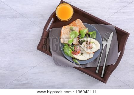 Homemade tasty breakfast with fried eggs on wooden tray