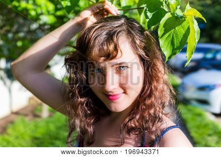 Closeup Portrait Of Young Brunette Woman's Face With Red Or Pink Lipstick Smiling Under Green Tree L
