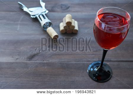Cup Of Pink Wine On Table With Corkscrew Aside