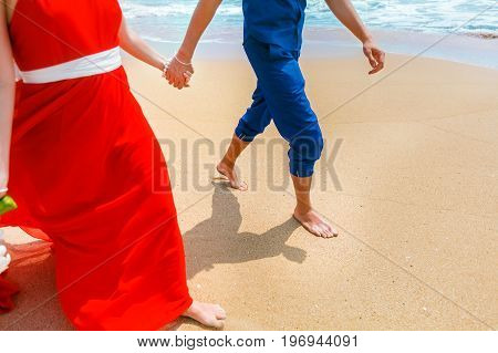 A couple walking together on the beach and holding hands. The woman dressed in red dress and man in the blue costume. Close-up