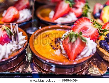 Macro Closeup Of Golden Creme Brulee Pots With Strawberries And Whipped Cream On Display In Bakery B