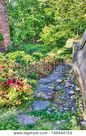 Private garden path with stones and red flowers and fence