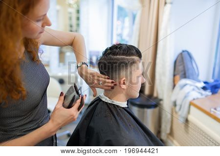 Girl Hairdresser With Curly Red Hair Cuts Young, Handsome Guy In A Beauty Salon