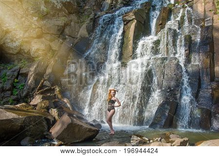 beautiful girl posing in a high waterfall, absolutely deserted redhead girl in a waterfall. in the taiga