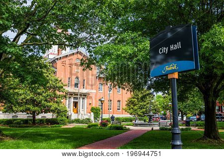 Frederick USA - May 24 2017: City Hall in downtown city in Maryland with brick building exterior sign and park square with flowers and police man