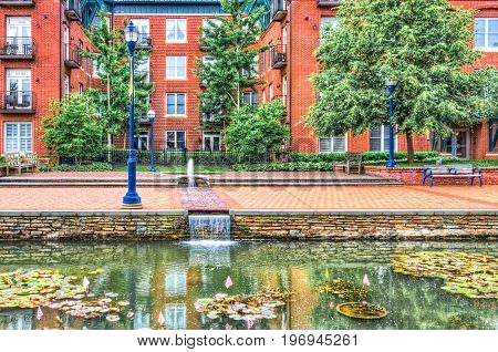 Frederick USA - May 24 2017: Carroll Creek in Maryland city park with canal reflection and lily pads with flags and bright red brick building