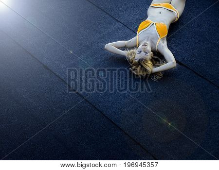 Blonde haired girl dressed in orange swimsuit lying on the roof. Copy space. Space for text. Sunshine