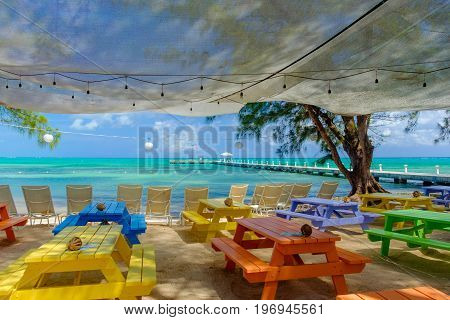 View of a jetty on the Caribbean sea from a beach with sun loungers and colorful tables at Rum Point, Grand Cayman