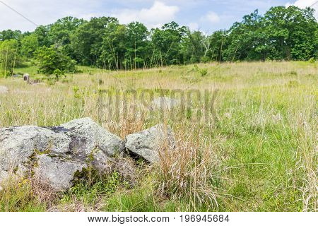 Gettysburg battlefield national park landscape with rock boulders and grave stones during summer with field