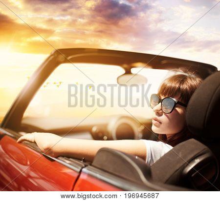 Young Caucasian woman in cabriolet car near sea