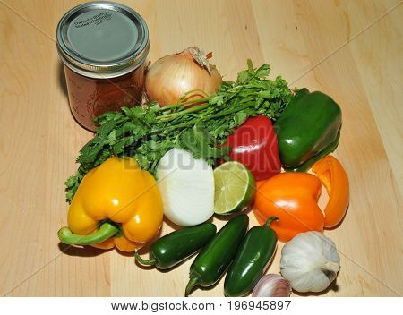 Fresh vegetables and homemade salsa on a wood cutting board