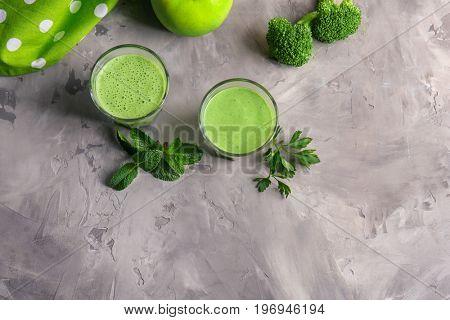 Glasses of fresh juice and apple on grunge background