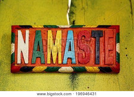 Colorful sign NAMASTE - the Sanskrit salutation - on old rustic wall