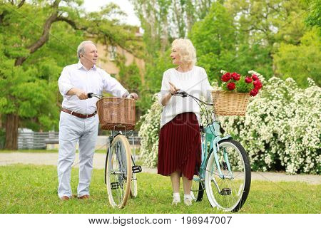 Senior couple walking with bicycles in spring park