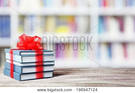 Books with ribbon bow as gift on wooden table at library