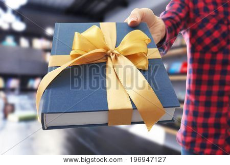 Woman holding book with ribbon bow as gift at library