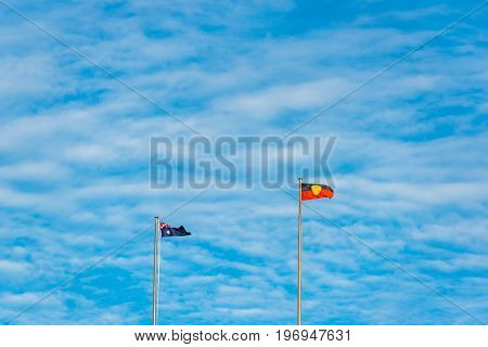 Australian and Australian Aboriginal flags against blue sky on the background. National symbol background