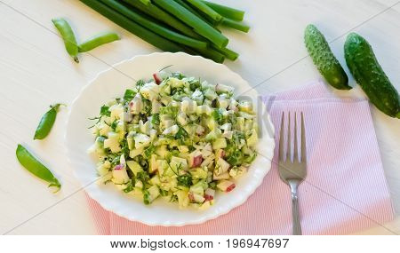 salad with radishes, cucumber greens and green onion sauce served on the side cucumbers and green peas