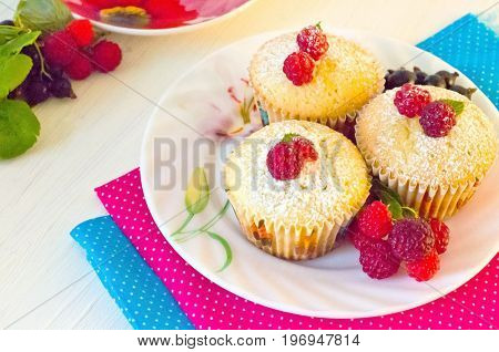 muffins with berries raspberries on colorful napkins