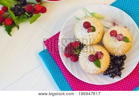 muffins with berries raspberries and black currants on the multi-colored napkins