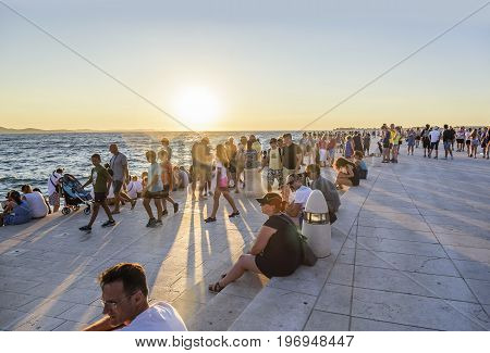 ZADAR, CROATIA - JULY 14, 2017: People listen to the Maritime Authority on the waterfront in Zadar, Croatia. Maritime Authority architectural structure created by architect Nikolai Basic in 2005.