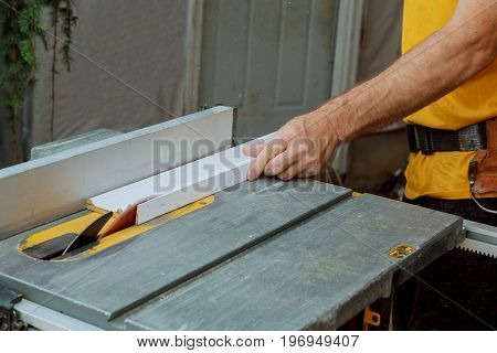 Unrecognizable handyman cutting wood on circular saw in the new house
