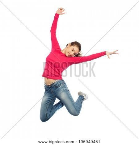 happiness, freedom, motion and people concept - happy young woman jumping or dancing in air over white background