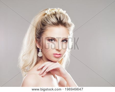 Portrait of gorgeous blond with a beautiful headband on a grey background.