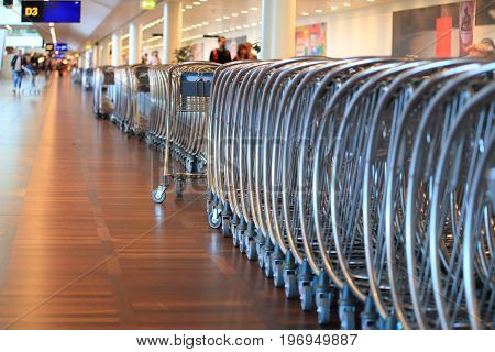 New shiny steel luggage trolleys in airport.Luggage trolleys standing in row.