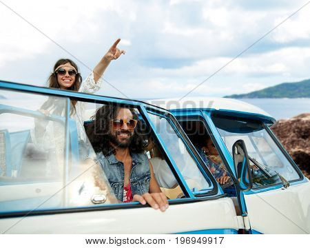 summer holidays, road trip, travel and people concept - smiling young hippie friends in minivan car over island and sea background