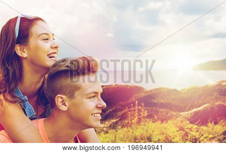 summer holidays, love and people concept - happy smiling teenage couple having fun over island and sea background