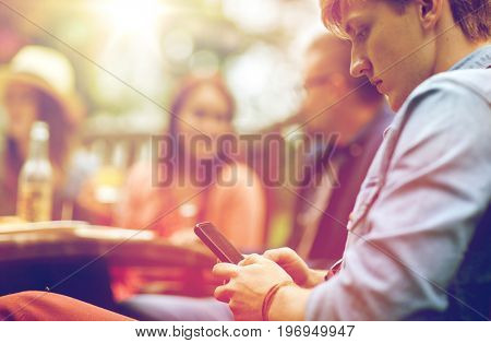 leisure, holidays, people and technology concept - young man texting on smartphone and friends having dinner at summer garden party