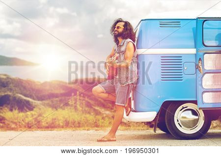 summer holidays, travel, music and people concept - young hippie man playing guitar and singing at minivan car over island and sea background