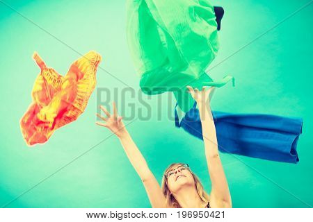 Cleaning in the closet fashion happiness concept. Woman throwing up lot of clothes. Clothing flying all over the place