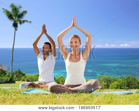 fitness, sport, yoga and people concept - happy couple meditating in lotus pose outdoors over exotic natural background with palm tree and ocean