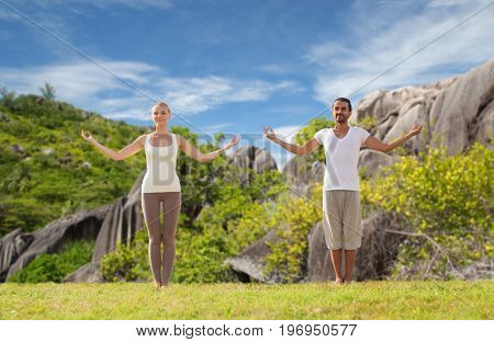fitness, sport and people concept - happy couple making yoga and meditating over natural background