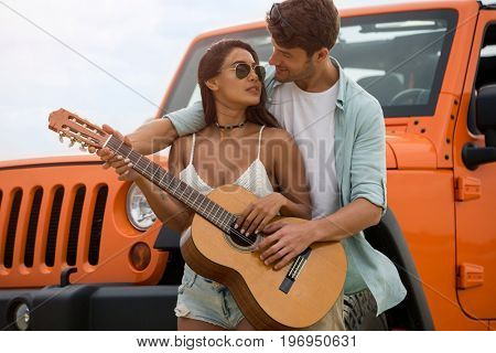Happy couple in love playing on a guitar together while standing near their car outdoors
