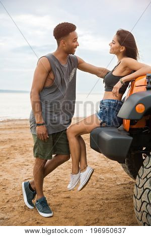 Happy young couple talking to each other while leaning on a car outdoors