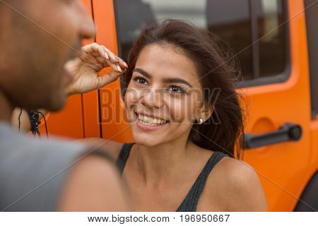 Close up of a smiling young woman talking to a guy while standing near a car outdoors