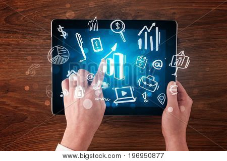 Caucasian business hands holding tablet with blue statistics and finances screen