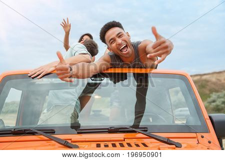 Happy excited afro american man having fun road trip with his friends